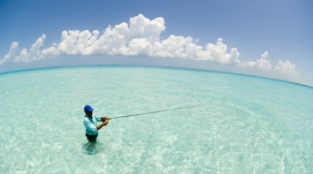 GREATER EXUMA BAHAMA, Fly fisherman casting for Bonefish in emerald green water. Fish Eye Panorama. Atlantic Ocean.  MR
